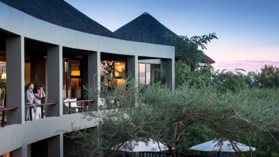hotels in heaven four season safari lodge serengeti accommodation couple binoculars trees terrace blue sky evening
