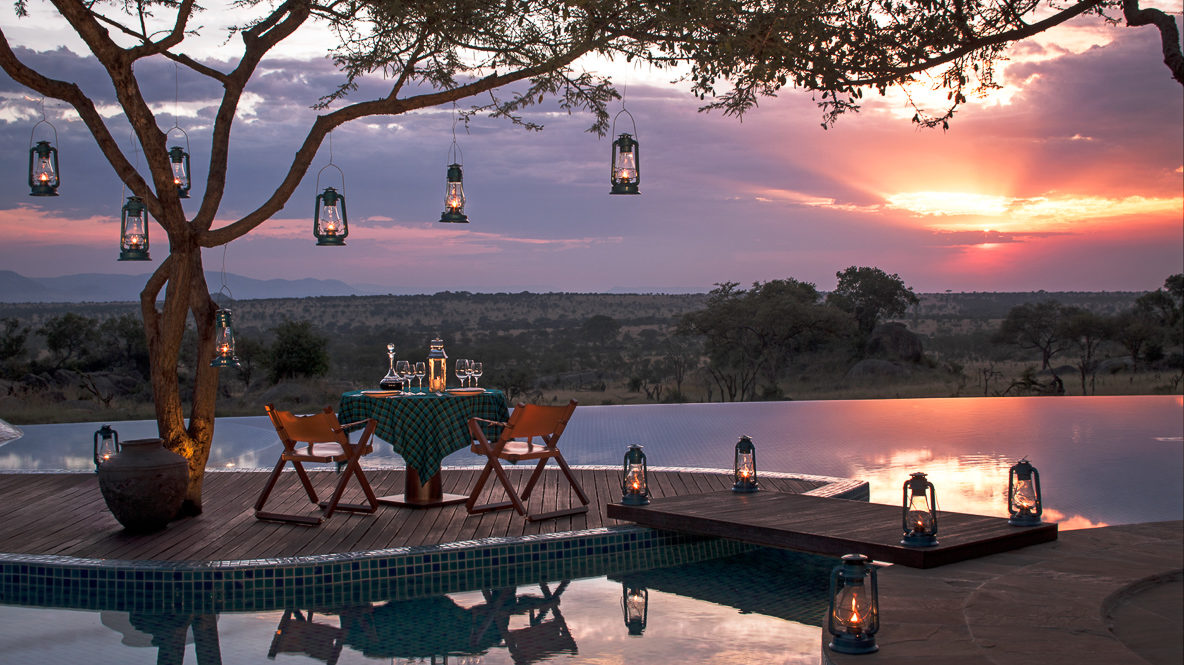 hotels in heaven four seasons safari lodge serengeti wooden bridge pool side table chairs wine lamps trees evening safari view