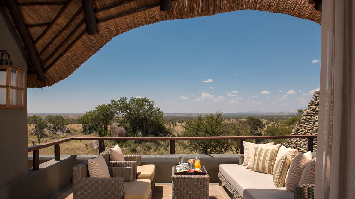 hotels in heaven four seasons safari lodge serengeti terrace sofa white cushions table breakfast trees blue sky sunny