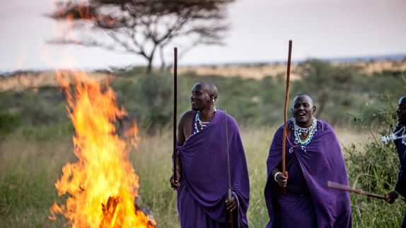 hotels in heaven four seasons safari lodge serengeti activity men violet robes fire sticks trees bushes natives