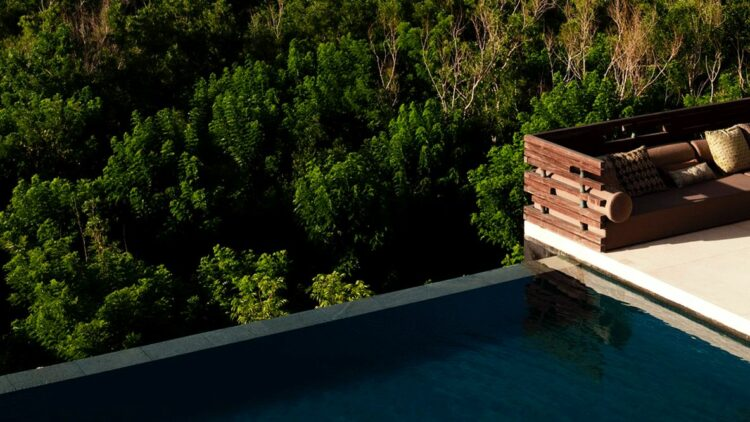 hotels in heaven alila villas uluwatu view forest pool trees wooden box on the edge green area