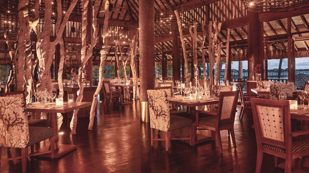 hotels in heaven four seasons bora bora culinary restaurant wooden floor chairs tables columns lights candles dishes dining
