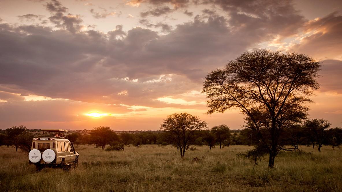 hotels in heaven safari lodge serengeti outdoors sunset jeep wheels trees grass veld ranger cloudy evening advertisement