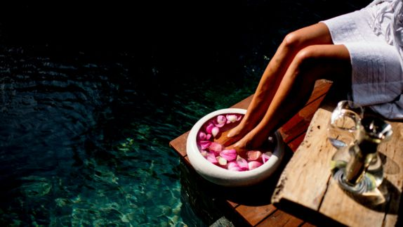 hotels in heaven Song Saa spa by Justin Mott petals glasses wine water woman tanned sun kissed towel