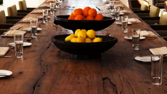 hotels in heaven alila villas uluwatu dining table fruit bowls lemons oranges glasses dishes fork wooden table