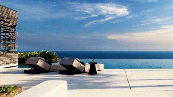 hotels in heaven alila villas uluwatu pool terasse ocean view sea wooden lounger bushes stone floor table