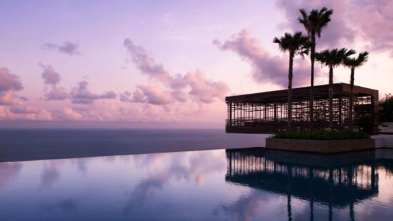 hotels in heaven alila villas uluwatu pool view sunset wooden cave sky colorful palm trees water grass bushes