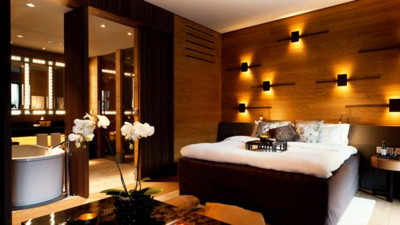 hotels in heaven chedi andermatt CAM Deluxe Room bathtub big bed lights flowers white orchids