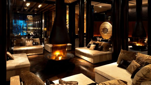 hotels in heaven chedi andermatt CAM Dining The Lobby fireplace bell lounge couch black chimney dark room