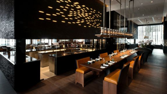 hotels in heaven chedi andermatt CAM Dining The Restaurant Commune Table kitchen wooden floor armchair leather