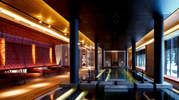 hotels in heaven chedi andermatt Spa Fitness Hydrothermal Pool red cushion armchairs light black columns stone strip