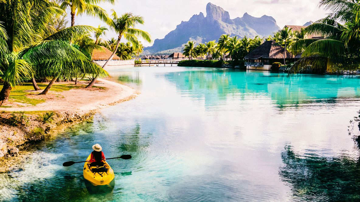 hotels in heaven four seasons bora bora activities kanu person kayak palm trees ocean sports adventure mountains