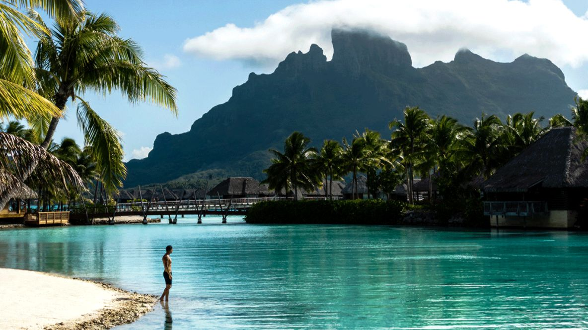hotels in heaven four seasons bora bora beachside mountains palm trees shacks person ocean water sky sunny cloudy