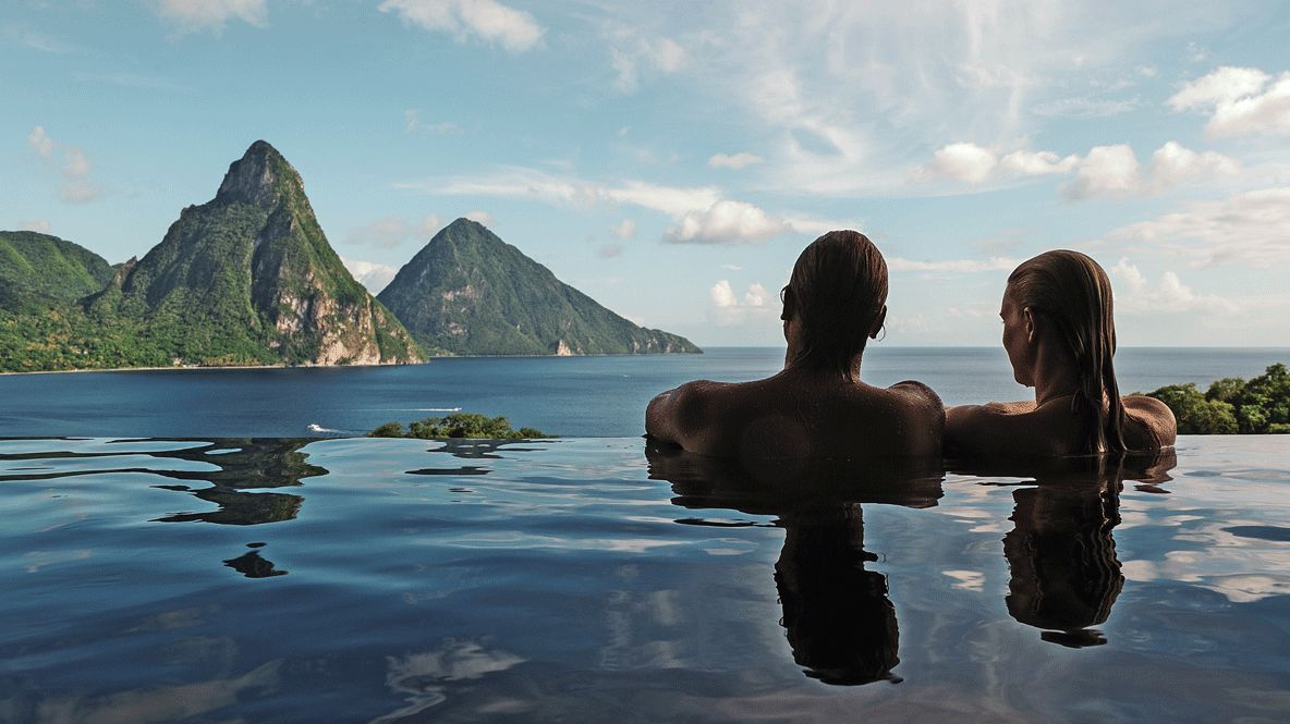 hotels in heaven jade mountain pool spa couple view woman man water sky cloudy sunny relaxing green grass cliffs