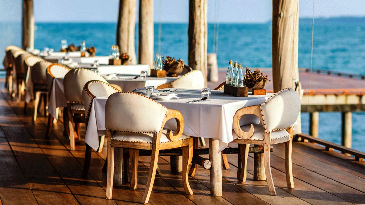 hotels in heaven song saa culinary restaurant wooden floor empty bottels chairs white tablecloth ocean