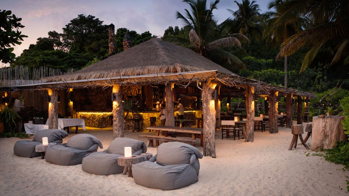 hotels in heaven song saa sunset driftwood grey beanbag chairs shack bar alcohol lights sand beach side people candles
