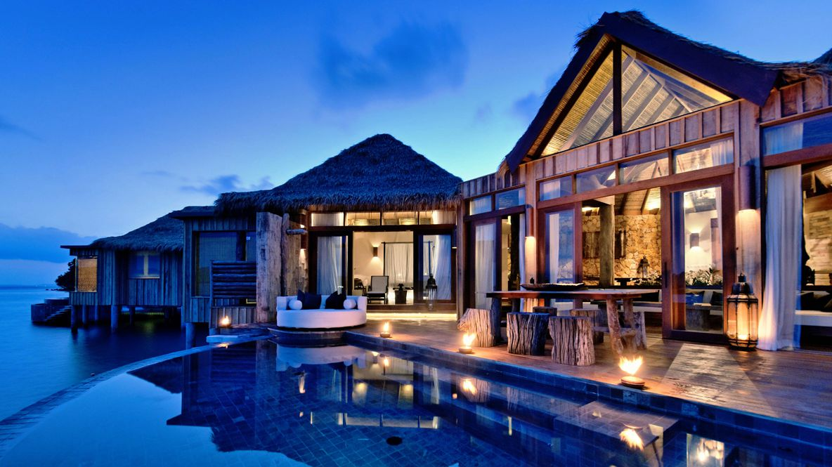hotels in heaven song saa bedroom infinity pool back deck at night wooden table chairs white sofa cushions lights house