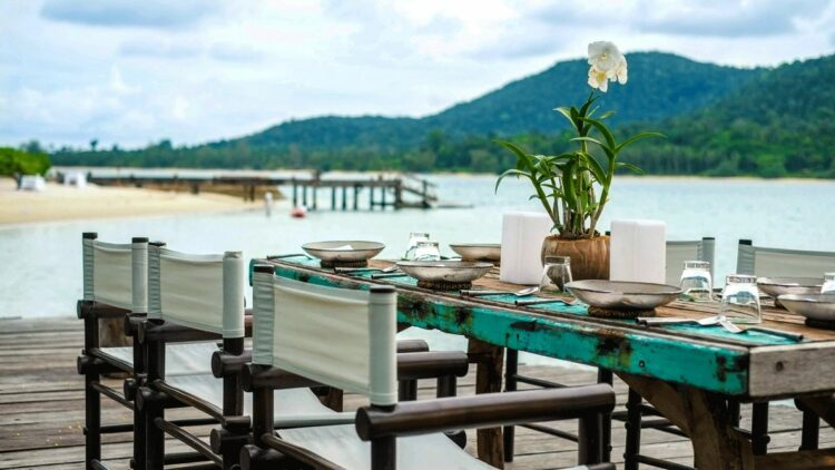 hotels in heaven song saa culinary table dinner bowls plates flower plant ocean beach side sand wooden floor chairs
