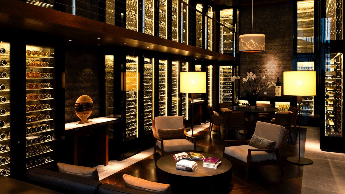 hotels in heaven chedi andermatt Dining The Wine Cigar Library cozy lounger dark room lamp books shelves