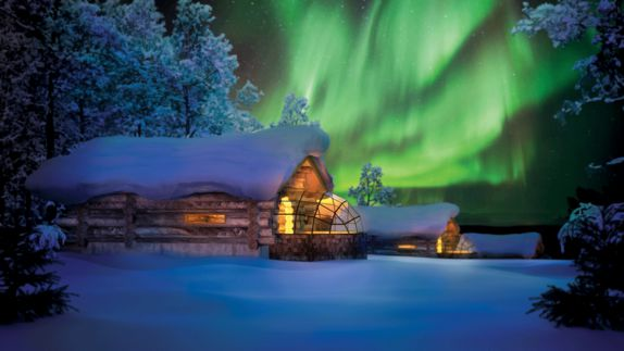 hotels in heaven Kakslauttane glass Igloo outdoor shacks wooden walls polar lights green trees snowy forrest snow