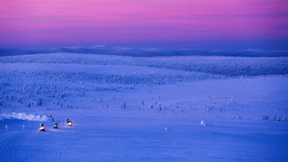 hotels in heaven Kakslauttanen snowmobile location fun race fast snow wide view evening no sun pink sky