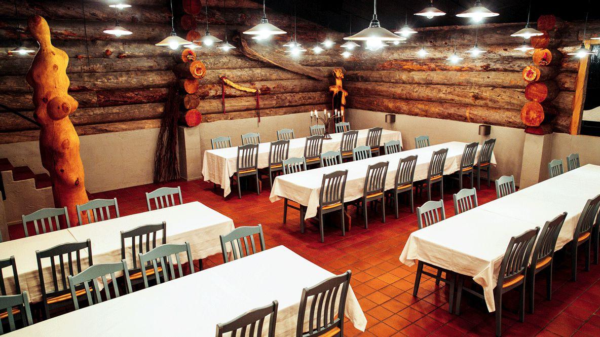 hotels in heaven Kakslauttanen Smoke Sauna Restaurant wooden floor columns chairs tables white table cloth lamps