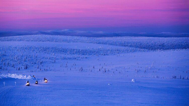 hotels in heaven Kakslauttanen snowmobile location fun race fast snow wide view evening no sun pink sky