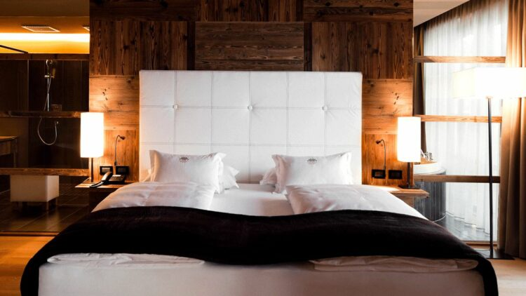 hotels in heaven alpina dolomites bedroomwindow side wooden wall floor white pillows white linen black coverlet