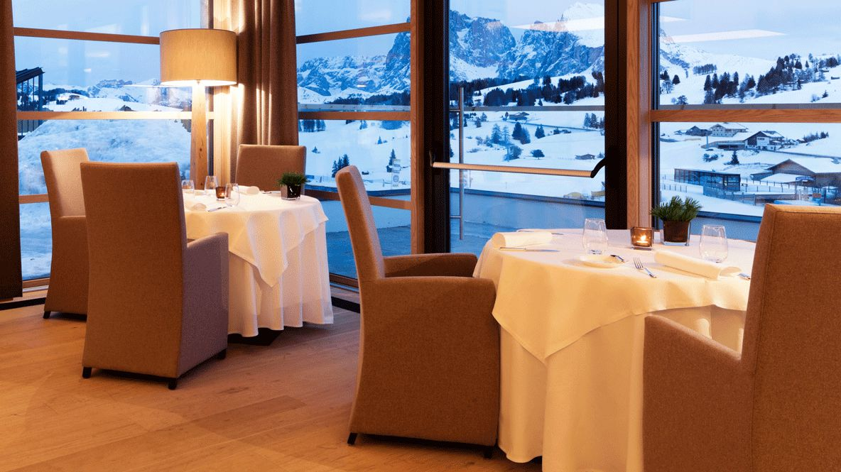 hotels in heaven alpina dolomites culinary lightbrown chairs wooden floor mountain view winter snowy lamp white tablecloth