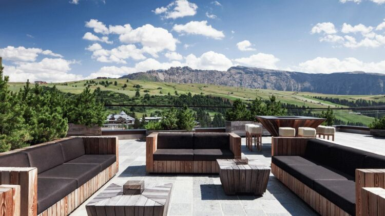 hotels in heaven alpina dolomites view terasse summer green grass stone floor wooden sofas black cushions