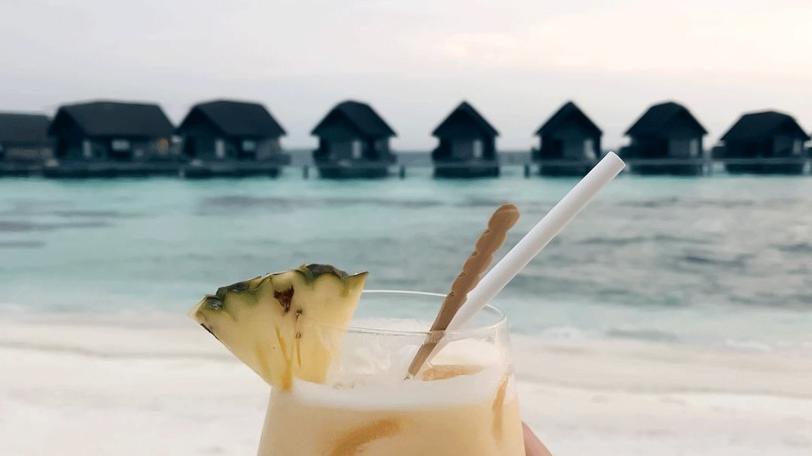 hotels in heaven como cocoa island culinary cocktail pina colada ananas pieces straw background houses shacks water turqoise