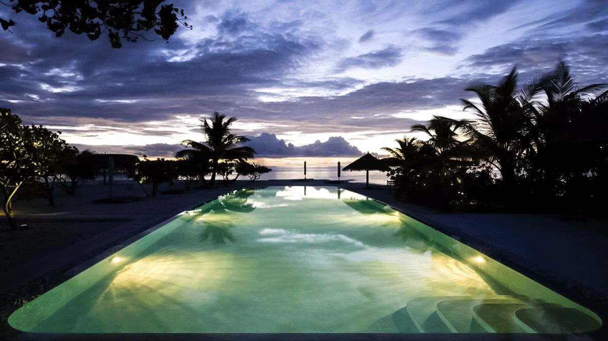 hotels in heaven como cocoa island pool night cloudy sky lights greenish water turqouise palm trees sun shades