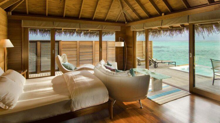 hotels in heaven conrad maldives rangali indoor bedroom villa ocean view white linen cushions pillows blankets sofa armchair