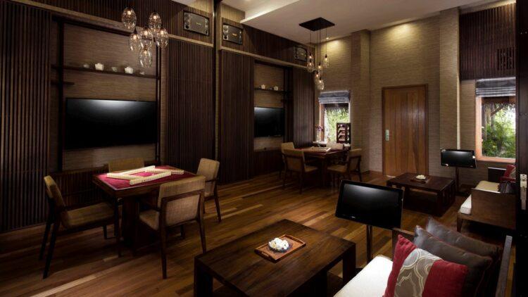hotels in heaven conrad maldives rangali culinary dark room wooden chairs floor tables brown cushions pillows sofa