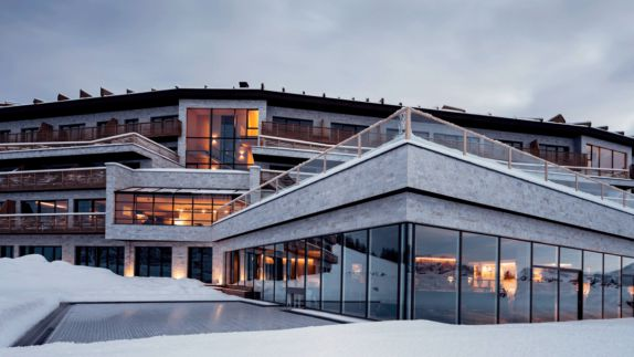 hotels in heaven alpina dolomites location hotel glass front view terrace lighted rooms stone frontage cloudy sky