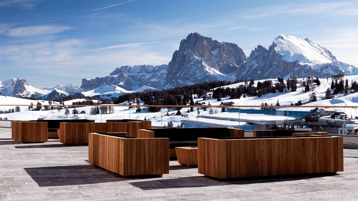 hotels in heaven alpina dolimites outdoor terasse view couches black cushions snowy mountaintops houses roof
