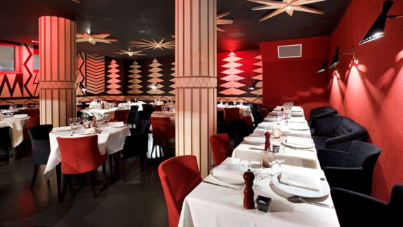 hotels in heaven altapura val thorens culinary restaurant red walls linen tables plates forks knives columns lights