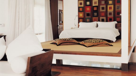 hotels in heaven como cocoa island room indoor bed big white linens red brown yellowish cushions wooden floor sofa