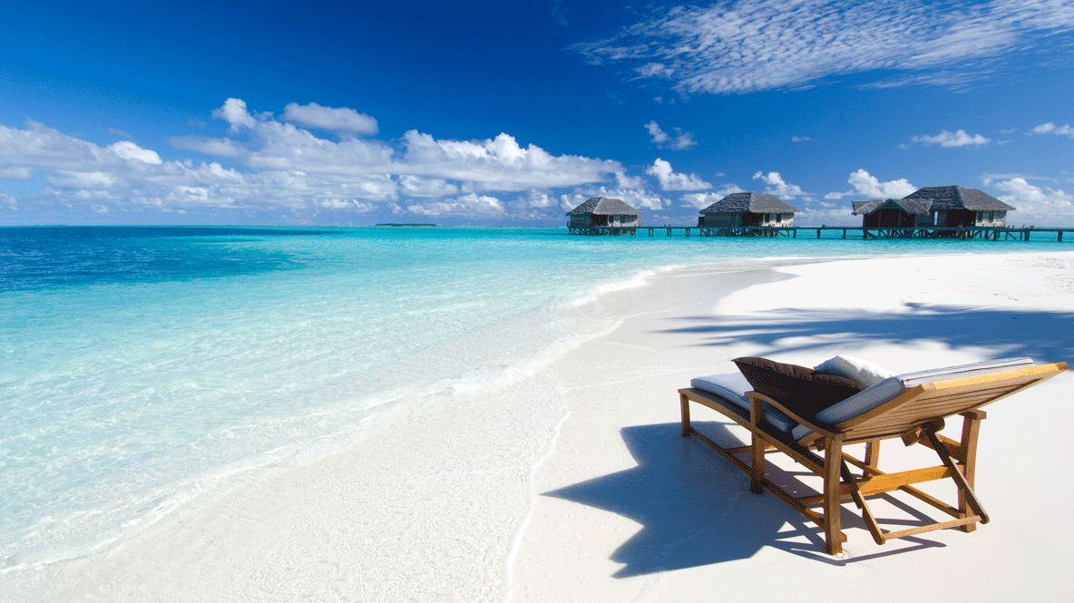 hotels in heaven conrad maldives rangali beach ocean view lounger wooden cushions water pillows turqouise clouds sky