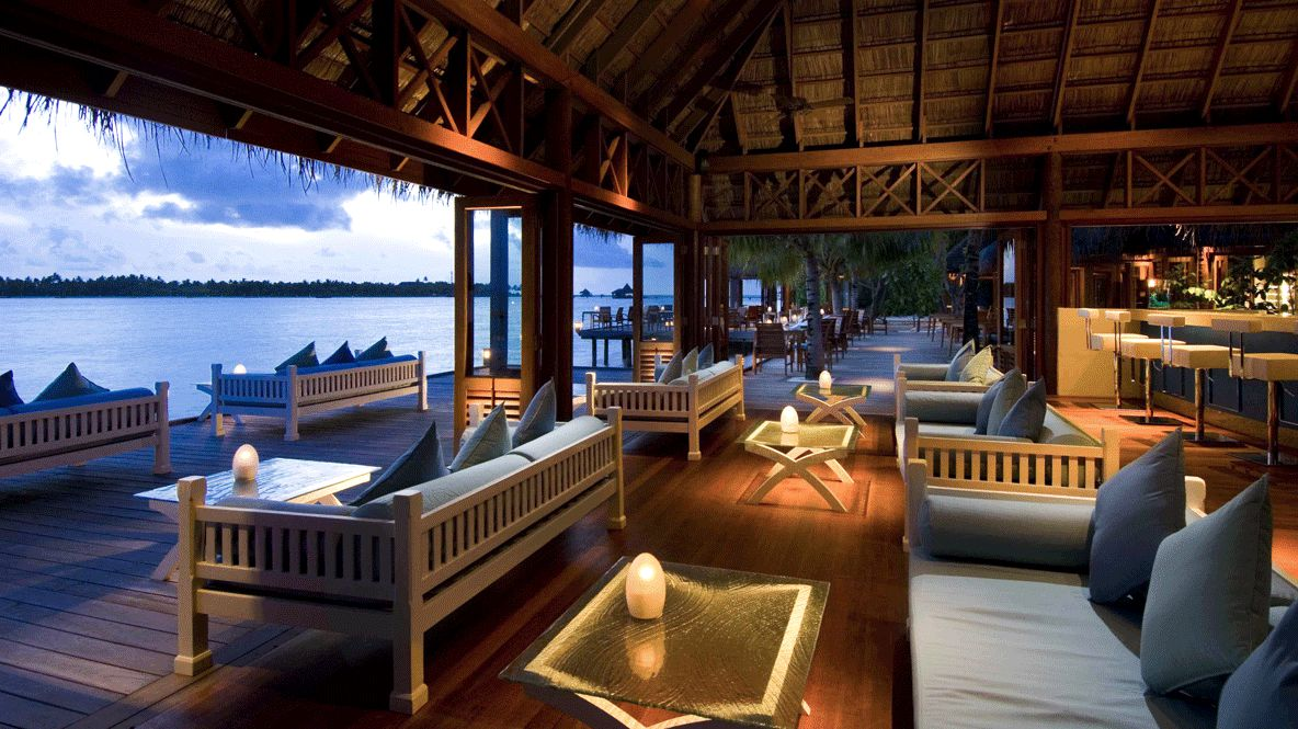 hotels in heaven conrad maldives rangali culinary bar wooden white sofas blue cushions ocean view glass tables greenish