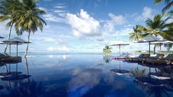 hotels in heaven conrad maldives rangali pool accommodation palm trees mirror water loungers cloudy sky ocean view