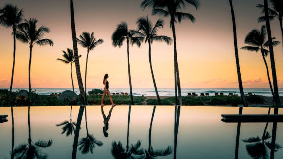 hotels in heaven four seasons hualalai pool mirror sunset beauty woman bathing suit ocean walking palm trees