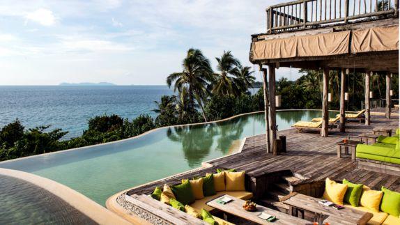 hotels in heaven soneva kiri culinary outdoor pool view water green yellow pillows palm trees ocean wooden floor