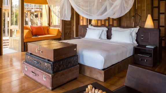 hotels in heaven soneva kiri room accommodation luxury big bed white blanket suitcases orange pillows sofa oriel reading place