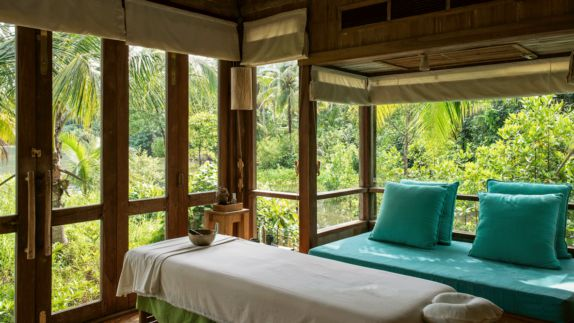 hotels in heaven soneva kiri spa luxury wellness massage table towel door windows palm trees bushes sound bowl