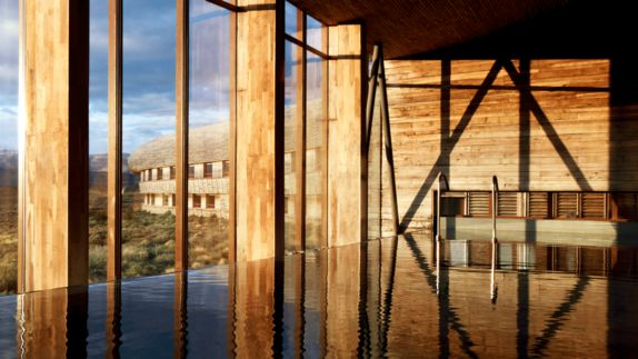 hotels in heaven tierra patagonia indoor pool water mirror sunny sun wooden columns walls grass outside outdoor view