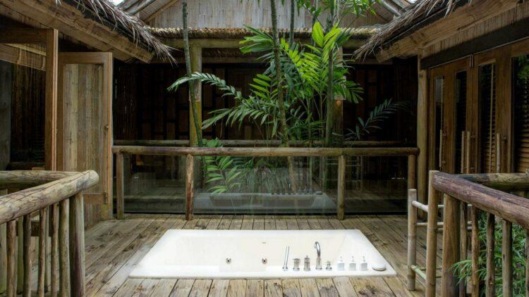 hotels in heaven soneva kiri bathtub luxury private bathtub wooden floor fence bushes plants tab glass window door