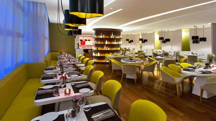 hotels in heaven w bogota culinary restaurant chair table candle plate dishes glass wine glass green light flower napkin