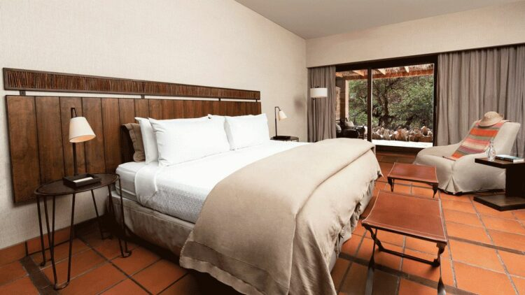 hotels in heaven alto atacama bedroom view luxury big bed white pillows blankets mattress table chairs wooden floor white wall armchair