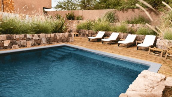 hotels in heaven alto atacama pool outdoor terrasse water bushes stone walls wooden floor lounger brown